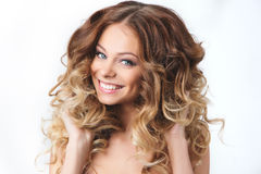 Porträt des schönen jungen lächelnden Mädchens mit dem luxuriösen Haarwinden Gesundheit und Schönheit Stockfotografie