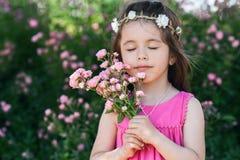 Porträt des schönen kleinen Mädchens mit Rosen blüht Stockfotos