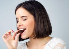Porträt des schönen lächelnden Mädchens, das Schokoladenplätzchen isst Lizenzfreie Stockbilder