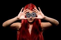 Porträt des schönen Mädchens mit Kreissägeblatt Bretty-Nackte, langes rotes Haar, nackter Körper, Sägeblatt, dunkler Hintergrund Stockbild