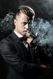 Porträt des sexy Mannes Havana rauchend Lizenzfreie Stockbilder