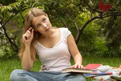 Porträt des Studenten mit Buch denkend an Prüfung Lizenzfreie Stockfotografie