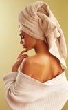 Porträt des tragenden Bademantels und des Tuches der jungen Schönheit auf ihrem Kopf im Schlafzimmer Lizenzfreie Stockfotografie