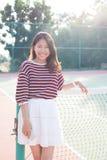 Porträt des tragenden weißen Kleidungsrockes der schönen jungen asiatischen Frau im Tenniskurs mit glücklichem Gesicht Lizenzfreie Stockfotografie