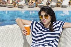 Porträt des trinkenden Safts der jungen Frau auf dem Pool Stockfotos