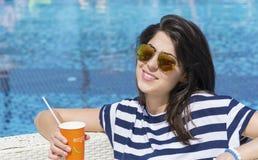 Porträt des trinkenden Safts der jungen Frau auf dem Pool Stockfotografie