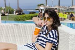 Porträt des trinkenden Safts der jungen Frau auf dem Pool Lizenzfreie Stockfotografie