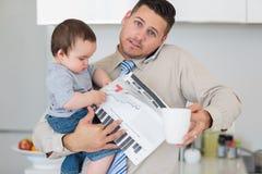 Porträt des Vaters mehrere Dinge gleichzeitig tuend im Haus Stockbild