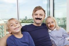 Porträt des Vaters und der Kinder mit dem künstlichen Schnurrbart zu Hause Lizenzfreies Stockfoto
