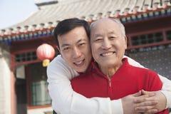 Porträt des Vaters und des Sohns außerhalb des Gebäudes des traditionellen Chinesen Stockfotos