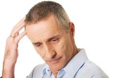 Porträt des verwirrten Mannes seinen Kopf verkratzend Stockfotos