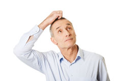 Porträt des verwirrten Mannes seinen Kopf verkratzend Stockfotografie