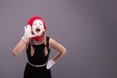 Porträt des weiblichen Pantomimen im roten Kopf und mit Weiß Stockbild