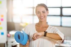 Porträt des weiblichen Unternehmensleiters, der Übungsmatte hält Stockbilder
