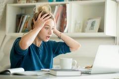 Porträt einer attraktiven Frau bei Tisch, die ihren Kopf ergreift Lizenzfreie Stockfotos