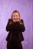 Porträt einer überraschten jungen Frau in einem schwarzen Anzug Stockfotografie