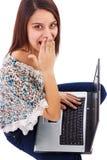Porträt einer überraschten jungen Frau mit dem Laptop, der oben schaut Lizenzfreie Stockfotos