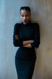 Porträt einer ernsten afrikanischen oder schwarzen amerikanischen Frau mit den Armen faltete Stellung über grauem Hintergrund und Stockfotos