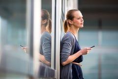 Porträt einer glatten jungen Frau, die um einen Smartphone ersucht Lizenzfreie Stockfotografie