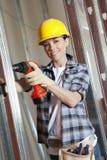 Porträt einer glücklichen mittleren erwachsenen Arbeitnehmerinbohrung an der Baustelle Stockbilder