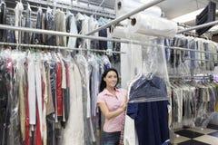 Porträt einer glücklichen mittleren erwachsenen Frau, die Plastik setzt, um zu trocknen, säuberte Kleidung in der Wäscherei Lizenzfreie Stockfotos