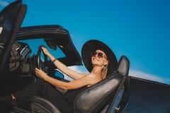 Porträt einer jungen Dame im Auto in einem großen schwarzen Hut Stockbilder
