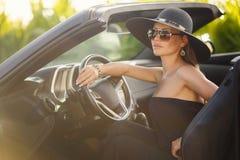 Porträt einer jungen Dame im Auto in einem großen schwarzen Hut Stockbild
