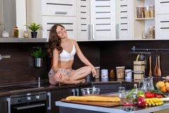 Porträt einer jungen dünnen Frau in der Wäsche in der Küche Stockfotos