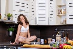 Porträt einer jungen dünnen Frau in der Wäsche in der Küche Stockfotografie