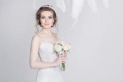 Porträt einer jungen und träumerischen Braut in einem luxuriösen Spitzehochzeitskleid Stockbilder