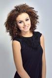 Porträt einer lächelnden gelockten behaarten europäischen Frau Lizenzfreies Stockfoto