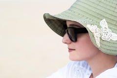 Porträt einer schönen jungen Frau in der Sonnenbrille und im grünen Hut Lizenzfreies Stockfoto