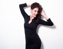 Porträt einer schönen netten Sinnlichkeitsfrau im schwarzen Kleid, das über weißem Hintergrund aufwirft Lizenzfreie Stockfotografie