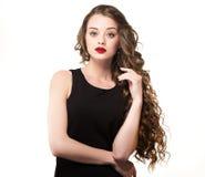 Porträt einer schönen Sinnlichkeitsfrau im schwarzen Kleid mit dem langen gelockten Haar Lizenzfreies Stockfoto