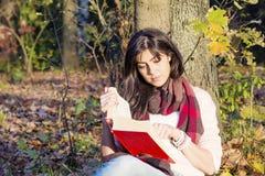 Porträt einer Schönheit, die auf einem Baum mit Buch im Herbstpark sich lehnt Stockfotos