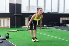 Porträt einer Sitzfrau, die mit dem Barbell tut deadlift, Rückenmuskulatur und Arme ausarbeitend trainiert Stockbild