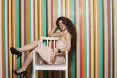 Porträt einer verlockenden jungen Frau, die auf Stuhl gegen bunten gestreiften Hintergrund sitzt Lizenzfreie Stockfotos