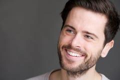 Porträt eines attraktiven jungen Mannes, der auf grauem Hintergrund lächelt Stockfoto