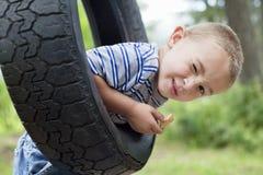 Porträt eines blinzelnden Jungen beim Schwingen auf Reifen Stockfotografie