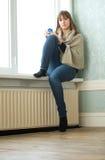 Einsames Mädchen, das im leeren Raum sitzt Stockfotos