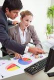 Porträt eines ernsten Geschäftsteams, das Statistiken studiert Lizenzfreie Stockfotos