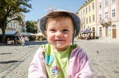 Porträt eines glücklichen kleinen Babys in einem Denimhut und -jacke das lachend, das Ihre Gefühle, gehend auf den Markt Squar au Lizenzfreie Stockfotos