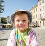 Porträt eines glücklichen kleinen Babys in einem Denimhut und -jacke das lachend, das Ihre Gefühle, gehend auf den Markt Squar au Stockfotografie