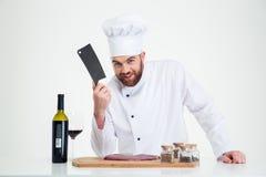 Porträt eines glücklichen männlichen Chefkochs, der Fleisch zubereitet Lizenzfreies Stockbild