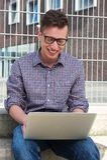 Porträt eines glücklichen Studenten, der draußen an Laptop arbeitet Stockfotos