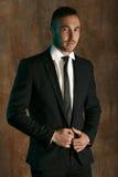 Porträt eines gutaussehenden Mannes in einem schwarzen Anzug, der über Wandhintergrund aufwirft Lizenzfreies Stockbild