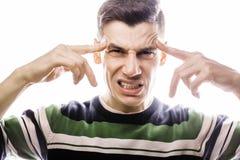 Porträt eines intelligenten ernsten jungen Mannes, der gegen weißen Hintergrund steht Emotionales Konzept für Geste Lizenzfreie Stockfotografie