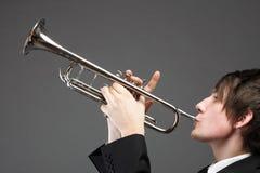 Porträt eines jungen Mannes, der seine Trompete spielt Lizenzfreie Stockbilder