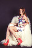 Porträt eines jungen schönen Mädchens mit dem langen Haar in einem weißen Kleid mit Blumen in den roten Pantoffeln im Studio auf  Lizenzfreies Stockfoto