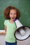 Porträt eines jungen Schulmädchens, das durch ein Megaphon schreit Lizenzfreies Stockfoto
